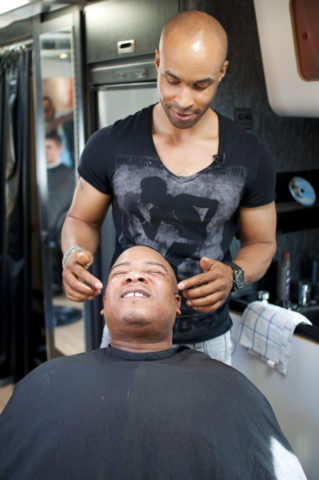 Julian Payne, owner and barber of The Original Mobile Barbershop Co. puts the final touches on his customer's hair at the March 12 Get Fed event outside the Federal Bar in North Hollywood.